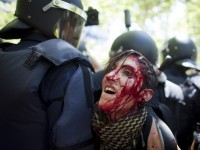 An injured protester is detained by riot police during clashes at the end of a march by Spanish coal miners in Madrid